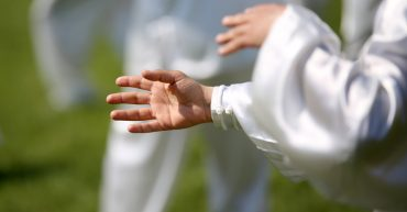 Claudios Martial Arts Intermediate Teen/Adult. Hand of martial arts master with followers
