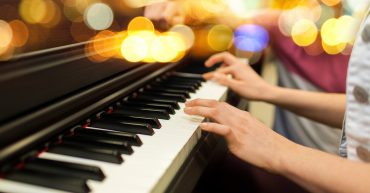 Intermediate Piano. Close up of woman hands playing piano over lights