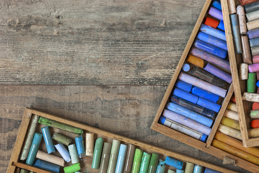 Old wooden boxes with colored pastel crayons lie on a textured wooden table